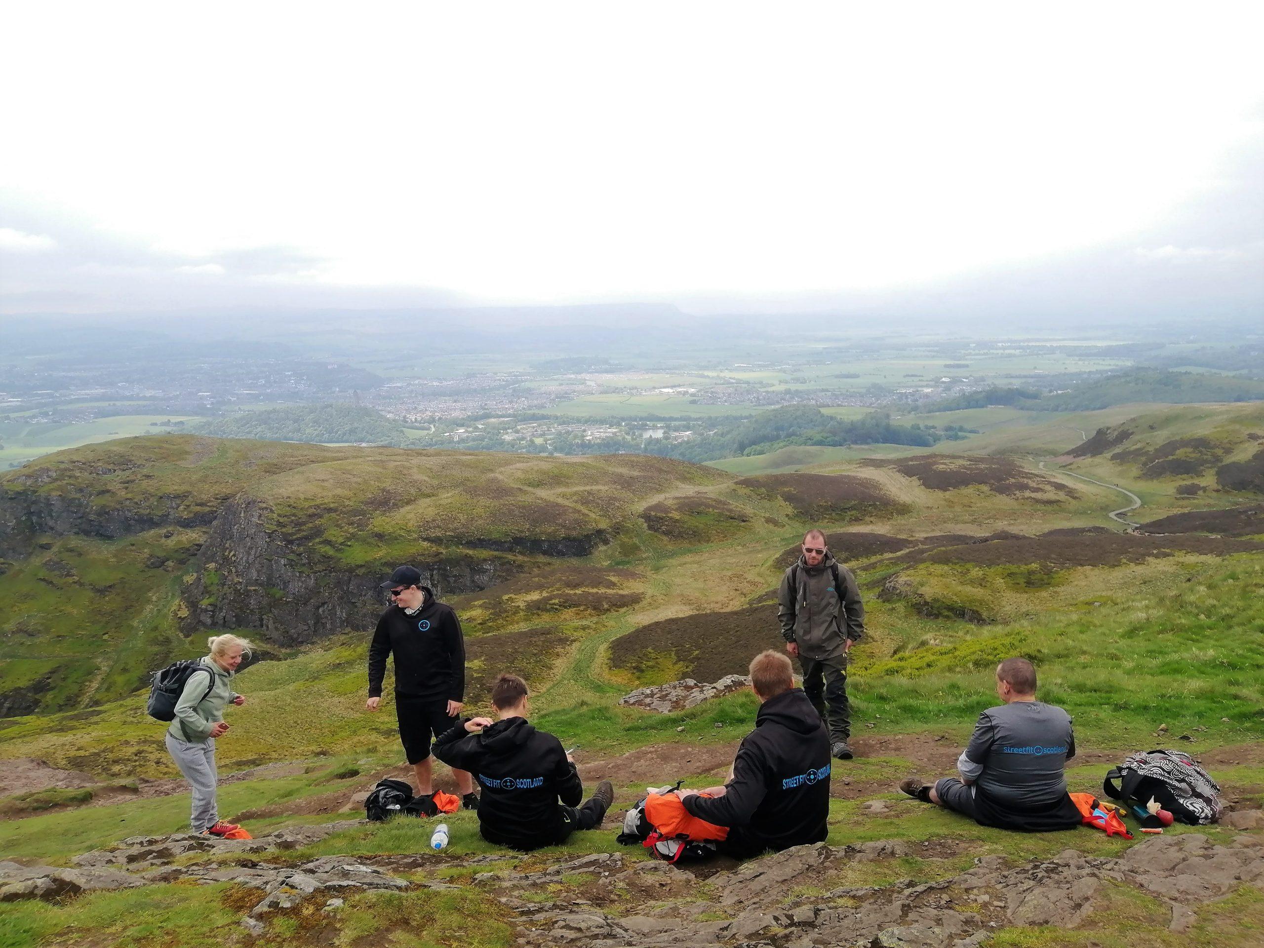 Group having lunch on hillside